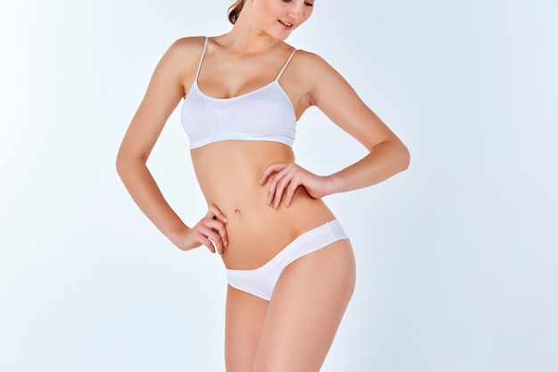 Молодая, стройная, здоровая и красивая женщина в белом белье