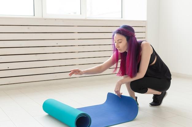 색 머리를 가진 젊은 슬림 힙 스터 소녀는 체조 스포츠 매트를 접고 체육관에서 수업 후