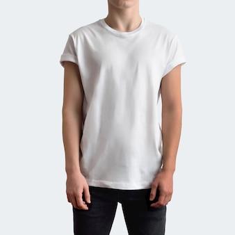 흰색 스튜디오 배경에 빈 티셔츠와 검은색 청바지를 입은 젊은 날씬한 남자. 모형은 쇼케이스에서 사용할 수 있습니다.