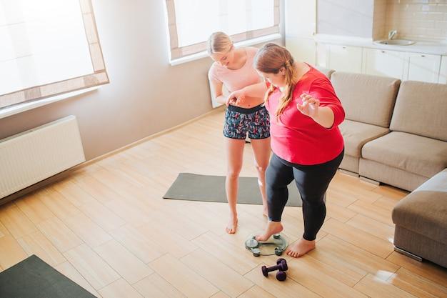 若いスリムなモデルは、太りすぎの女性がリビングルームで体重計の上に立つのに役立ちます。