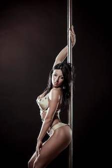 Young slim pole dance woman on a black studio background