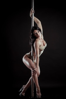 Giovane donna sottile pole dance su uno sfondo nero studio