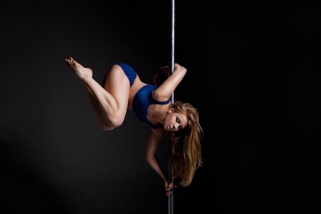 Молодая стройная женщина танца полюса упражнения на темном фоне