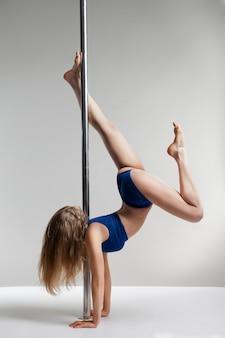 Молодая стройная женщина танца полюса упражнения на светло-сером заднем