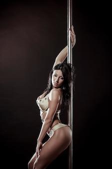 黒のスタジオの背景に若いスリムなポールダンスの女性