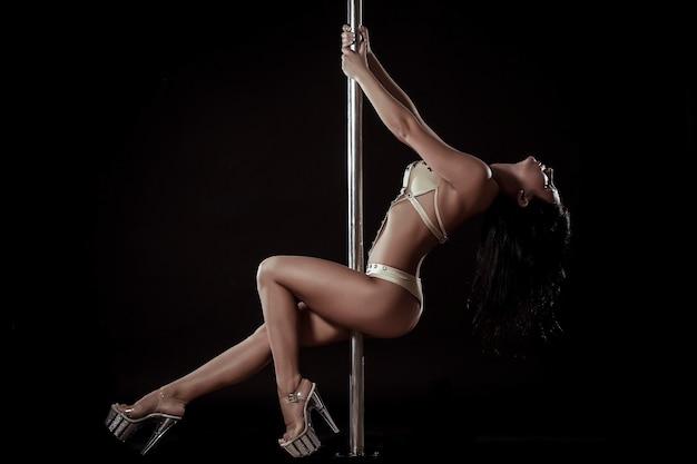 Молодая стройная женщина танец полюса на фоне черной студии