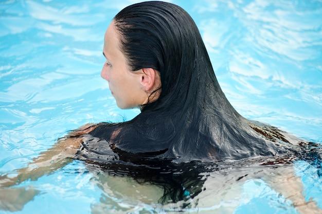 Молодая стройная сексуальная девушка в бикини с развевающимися волосами на брюнетке женщина в купальнике на песчаном пляже на фоне волн