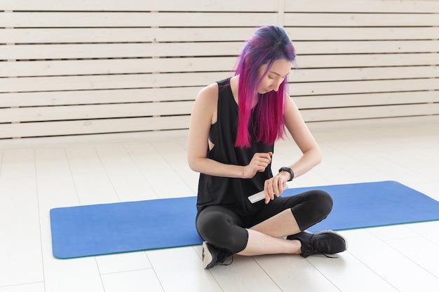 Молодая стройная неизвестная женщина с фиолетовыми волосами смотрит пульс и сжигает калории с помощью часов и смартфона, сидя на спортивных ковриках в тренажерном зале. концепция приложения для спорта