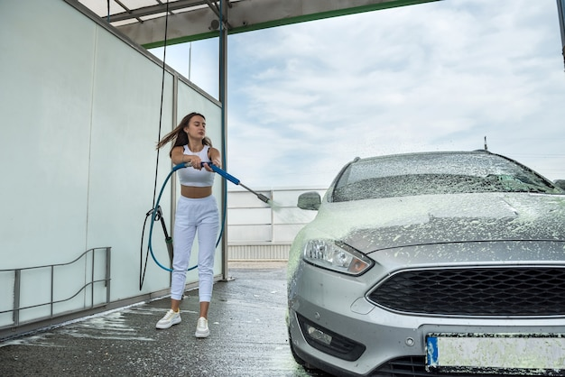 Young slim woman applies foam on her auto in self-service car wash station
