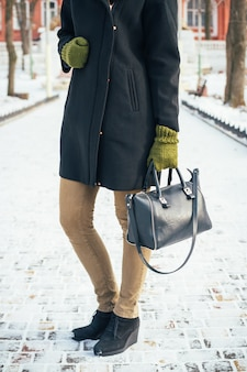 Young slim woman in a black coat and green gloves holding a handbag and standing on the snowy sidewalk