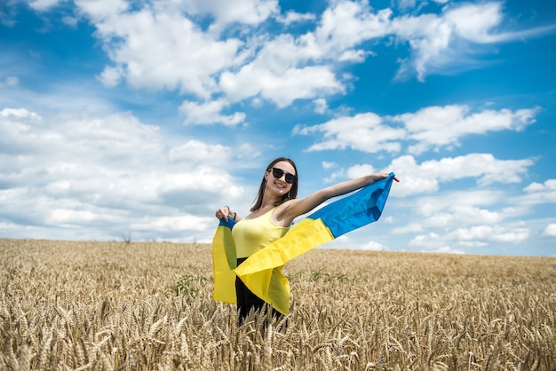 Young slim woman in blue-yellow flag of ukraine on wheat field in summer
