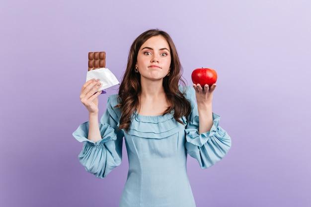 La giovane donna sottile sceglie fra la mela sana e il cioccolato dolce. bruna non sa decidere cosa mangiare a pranzo.