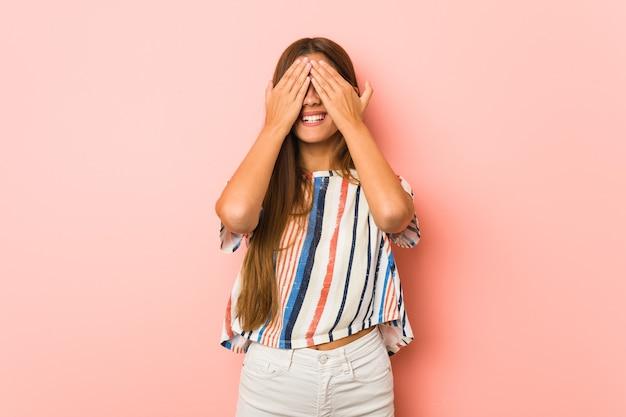 若いスリムな女性は手で目を覆い、驚きを広く待っている笑顔。