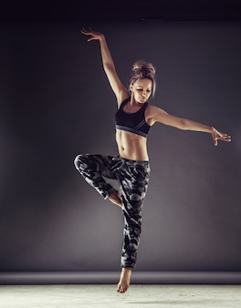 Young slim woman dancer in sports clothing jumping high on wall background