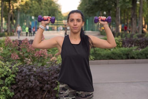Молодая стройная женщина делает упражнения с гантелями на открытом воздухе