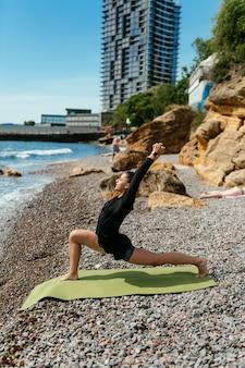 Giovane donna sottile che fa esercizio sulla stuoia di yoga all'aperto alla spiaggia di ciottoli in riva al mare