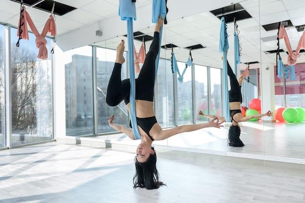 Молодая стройная женщина делает расслабляющее упражнение по воздушной йоге в гамаке в студии после тяжелого рабочего дня