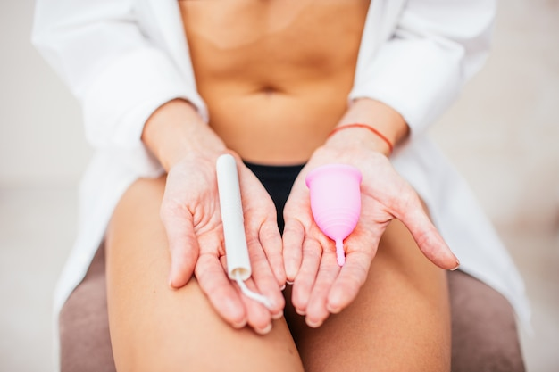 Young slim woman holding different types of feminine hygiene products - menstrual cup and tampon. womans periods concept. ecology choosing concept.