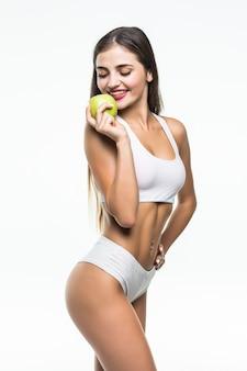 Молодая стройная женщина, держащая зеленое яблоко. изолированные на белой стене. концепция здорового питания и контроль избыточного веса.