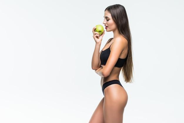 Giovane donna esile che tiene mela verde. isolato sul muro bianco. concetto di cibo sano e controllo del peso in eccesso.