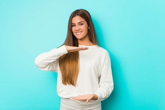 Young slim woman holding something with both hands, product presentation.