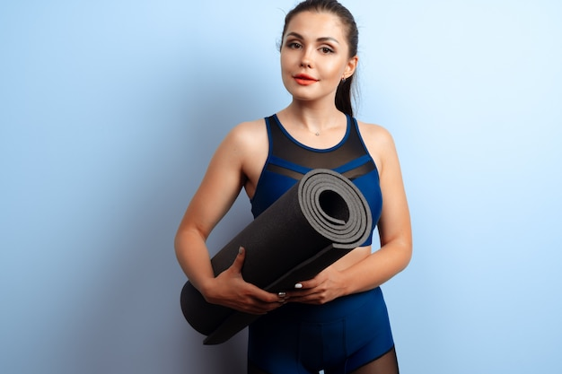 Young slim woman holding yoga fitness mat in her hands