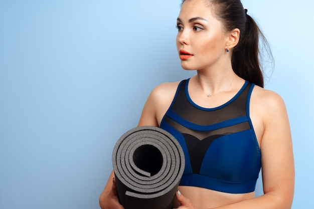 Молодая стройная женщина, держащая в руках коврик для йоги и фитнеса