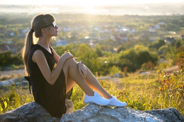 夏の日没で屋外でリラックスした岩の上に座っている黒のショートドレスの若いスリムな女性。