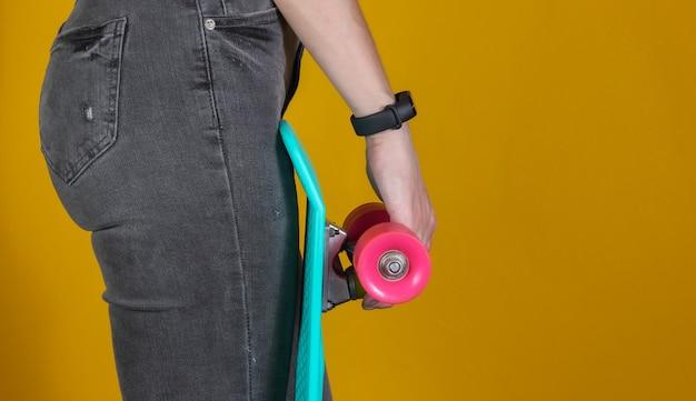 Молодая стройная женщина в джинсах держит в руках пластиковую доску круизера на желтом фоне. молодежная хипстерская мода. летнее веселье.