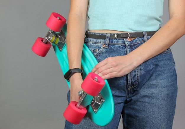 Молодая стройная женщина в джинсах держит в руках пластиковую доску для скейтбординга на сером фоне. молодежная хипстерская мода.