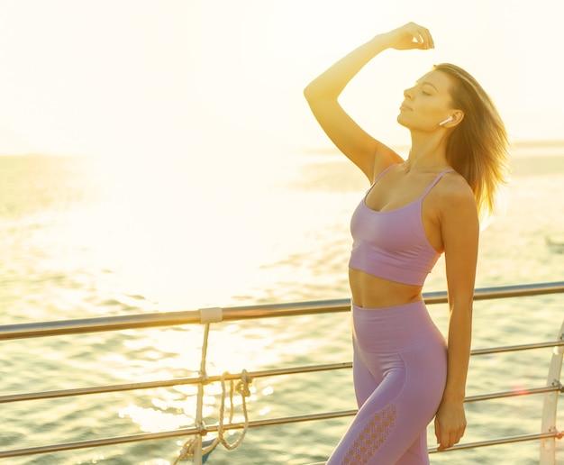그녀의 귀에 이어폰으로 음악을 즐기는 운동복에 젊은 날씬한 여자. 일출 아침 운동 개념