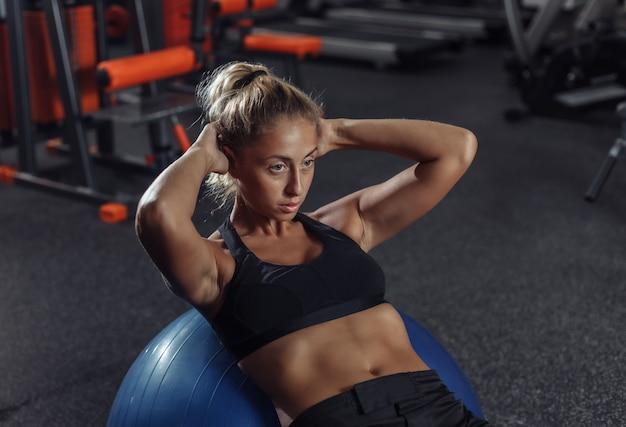 スポーツウェアの若いスリム女性がジムでフィットボールに腹部の筋肉をトレーニングします。