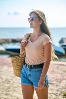 Молодая стройная женщина в солнцезащитных очках на пляже