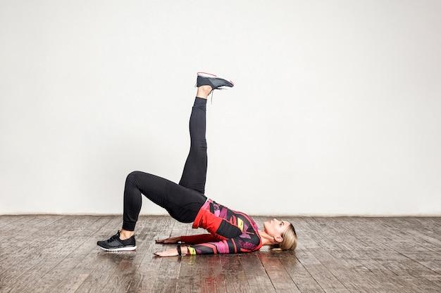 タイトなスポーツウェアを着た若いスリムな女性がヨガを練習し、脚を上げて片足のブリッジポーズをとり、柔軟性、筋力をトレーニングします。自宅でのヘルスケアとスポーツ活動。屋内スタジオショット