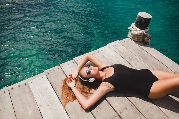 Молодая стройная женщина, лежащая на пирсе, средиземное море, лазурная вода, солнечная, загорелая кожа, слушающая музыка, наушники, черный купальник, сексуальное тело, солнечные ванны, тропический отдых, расслабленный, солнцезащитные очки