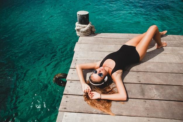 Giovane donna esile che pone sul molo, mar mediterraneo, acqua azzurra, sole, pelle abbronzata, ascolto di musica, cuffie, costume da bagno nero, corpo sexy, prendere il sole, vacanza tropicale, rilassato, occhiali da sole