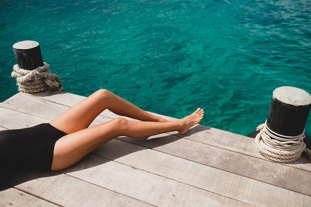 Giovane donna sottile che pone sul molo, mare, acqua azzurra, sole, pelle abbronzata, costume da bagno nero, corpo sexy, prendere il sole, vacanza tropicale, rilassato, gambe lunghe