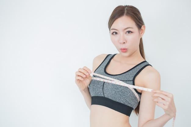 Молодая стройная женщина, измеряющая ее грудь с помощью рулетки