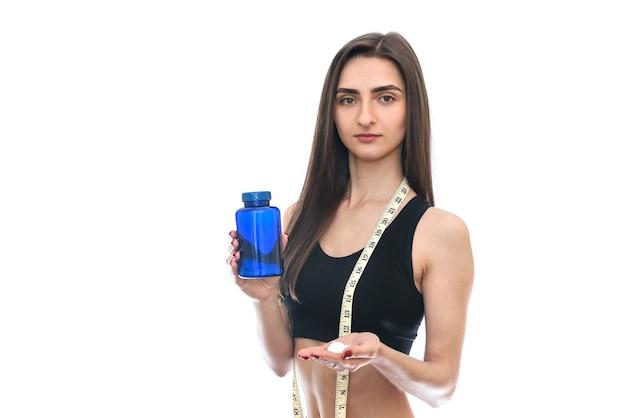 Молодая стройная женщина, предлагающая таблетки из бутылки