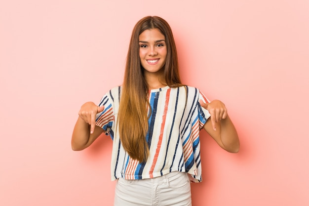 Young slim woman points down with fingers, positive feeling.