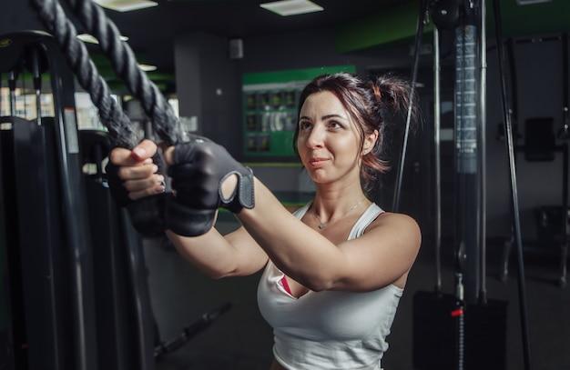 ジムのエクササイズマシンでロープで腕の延長を練習している若いスリムな女性