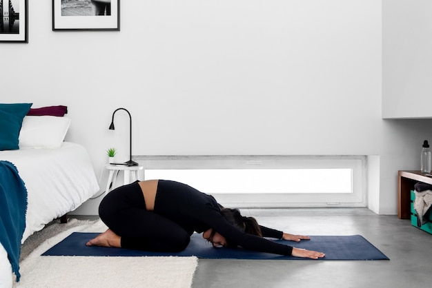 Young slim woman practicing yoga in extended child position in modern minimalistic bedroom at home