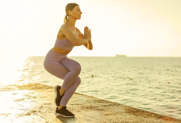 ヨガを練習している若いスリムな女性。日の出の瞑想。健康的なライフスタイルのコンセプト、バランス