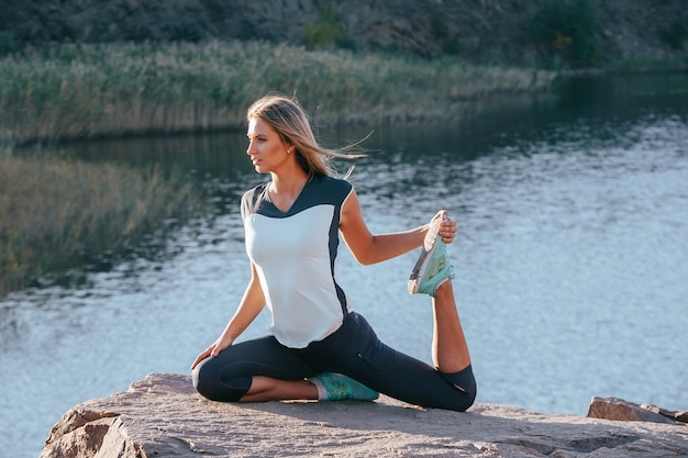 Young slim woman practicing yoga outdoors on stone