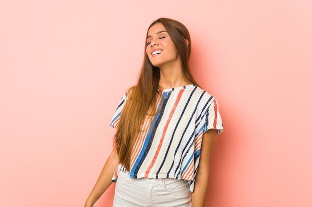 若いスリムな女性はリラックスして幸せな笑い、首を伸ばして歯を見せています。