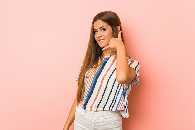 Young slim woman showing a mobile phone call gesture with fingers.
