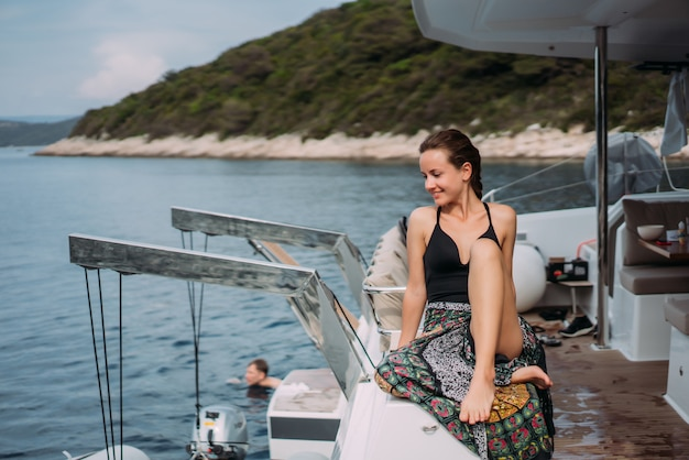 Молодая стройная женщина сидит в бикини купальный костюм на яхте и греется на солнце