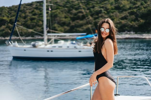 Молодая стройная женщина, сидящая в купальном костюме бикини на яхте в солнечных очках и греющаяся на солнце