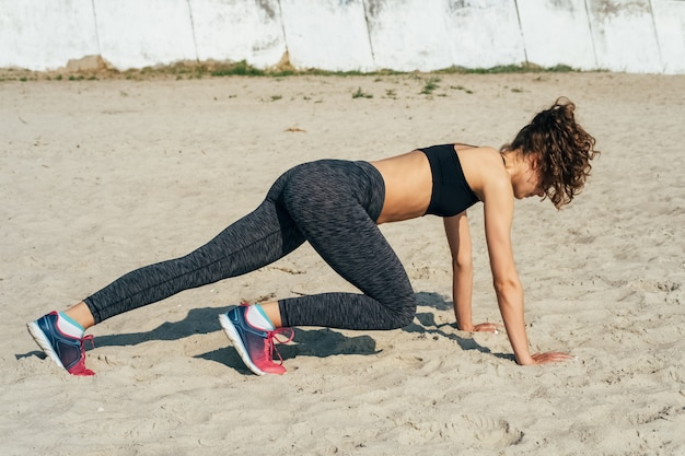 Young slim woman in sportswear doing exercise on the beach in the morning