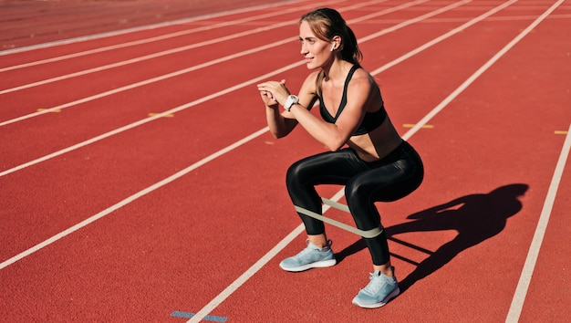 Young slim woman in sportswear doing squats exercise with rubber band on a red coated stadium track